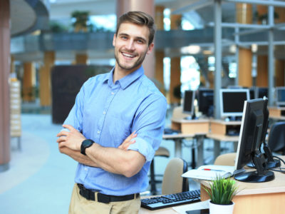 Young man posing confident and positive in professional workplace office with space